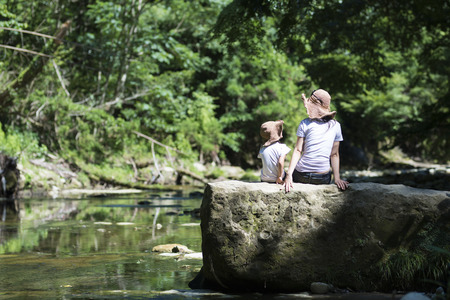 Mother and daughter playing on mountain stream