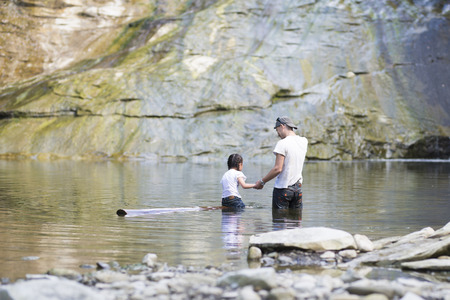 Father and daughter playing in the river Stock Photo