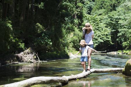 Moeder en dochter spelen in de bergstroom