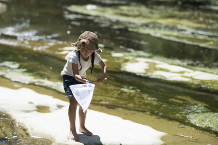 unexplored: Happy little girl playing on a stream