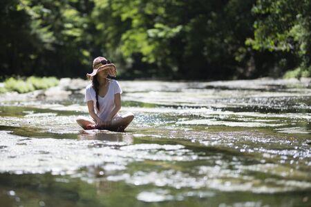 Beautiful woman relaxing in a mountain stream Imagens