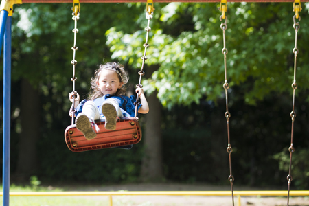 Happy Little Girl Playing With Swing Stock Photo