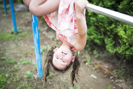 Little girl playing with an iron bar Stock Photo