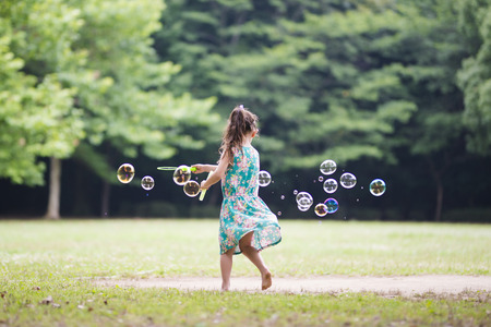 Little girl playing with soap bubbles 스톡 콘텐츠