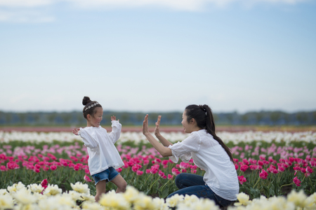 Mother and daughter playing in the tulip field Imagens