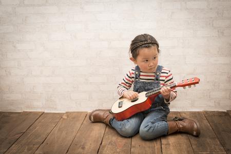 小さな女の子がギターを弾く