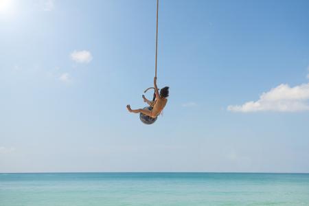Happy little girl swinging on the beautiful beach
