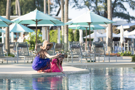 Mother and daughter at the poolside Stock Photo