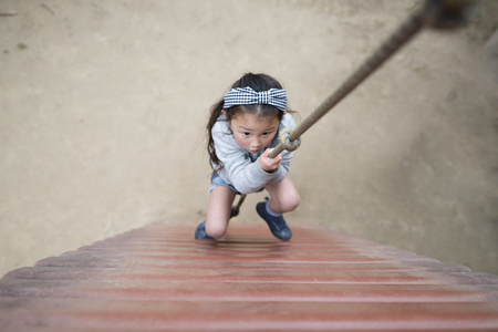 Cute little girl climbing up the rope Фото со стока