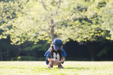 Little girl sitting on the green lawn 写真素材