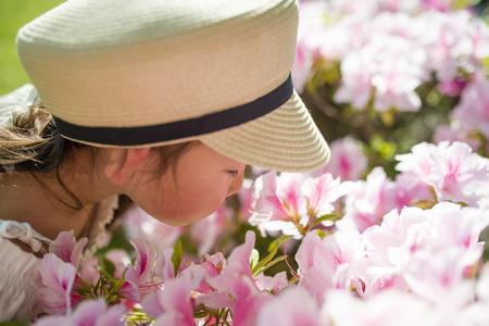 Pretty little girl sniffing flowers of azaleas