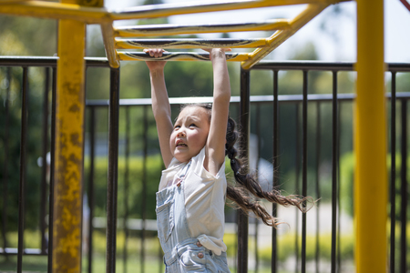 Little girl playing on monkey bars at park Stock Photo