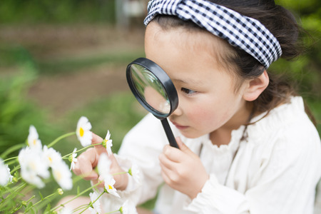 Little girl looking in a magnifying glass Stok Fotoğraf