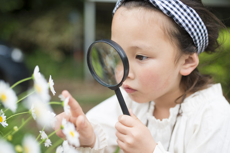 Little girl looking in a magnifying glass Фото со стока