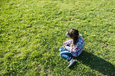 Happy little girl sitting on green lawn