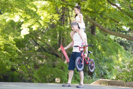 Père portant sa fille sur les épaules, vélo et planche à roulettes
