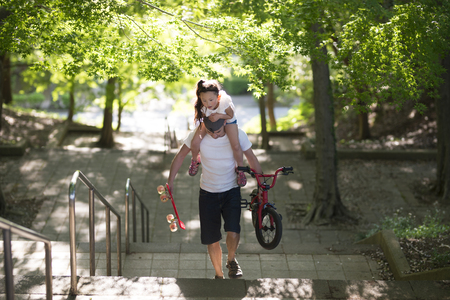 Father carrying her daughter on shoulders, bicycle and skateboard