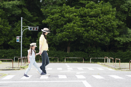 Mother and daughter walking on the pedestrian crossing