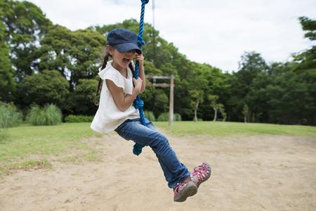 Little girl playing on the tarzan rope