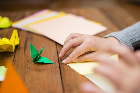 Childrens hands folding origami Stock Photo