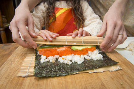 Mother and child making sushi roll together