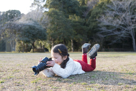 Little girl photographer is lying down to take  photos on the grass Stock Photo