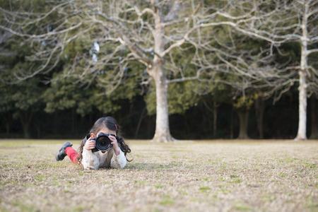 Little girl photographer is lying down to take  photos on the grass Foto de archivo