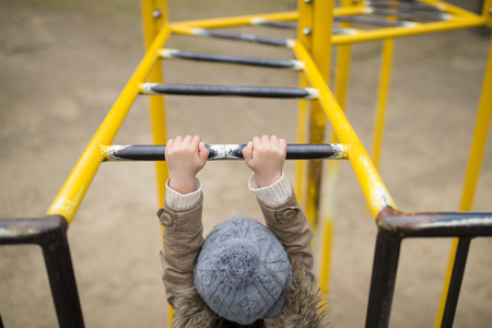 Little child playing on monkey bars Archivio Fotografico - 104888960