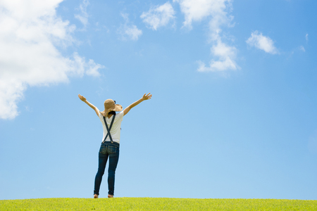 Happy woman standing in the summer field with her hands up toward sky