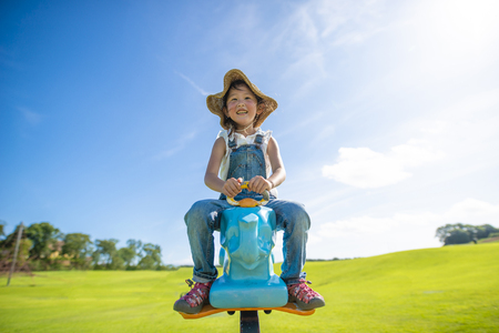 Happy little girl riding on the rocking horse on the green grass Stock Photo