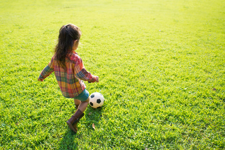 Cute little girl kicking a soccer ball on the green grass