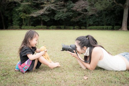 Happy young mother taking a picture of her daughter on the lawn 写真素材
