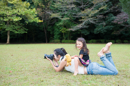 Happy young mother taking a picture and her daughter playing around her