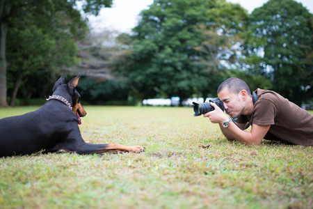 photography man and his doberman on a green grass