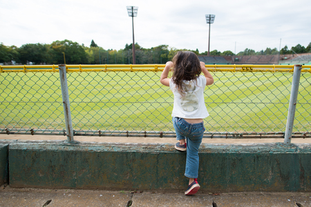 Little girl is in the baseball field of the stand