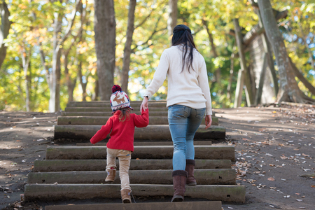 Rear view, mother and daughter climbing up the wooden stairs in the forest
