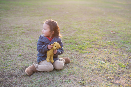 Cute little girl sitting on green grass with her teddy bear