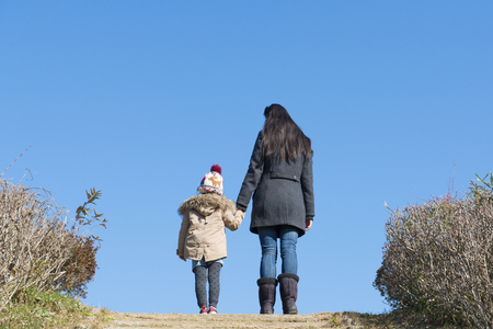 Back view of mother and daughter with blue sky back ground Stockfoto