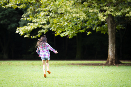 Girl wearing rain boots running on the green lawn