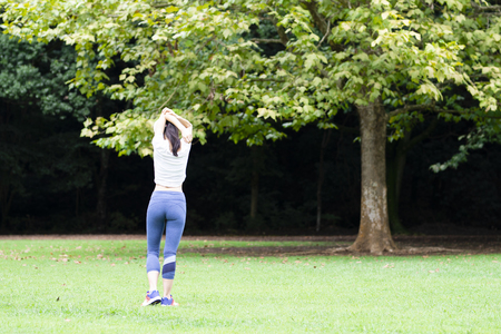 Rear view shot of slim young asian woman in the green park. fitness and weight loss concept 免版税图像