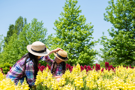 Mother and daughter playing in the flower field