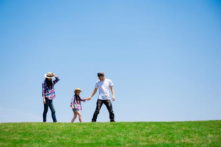 Padre, madre e hija jugando en la pradera