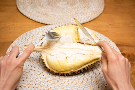 Hand holding a knife and fork and durian