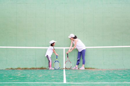 Mother and daughter practicing tennis Banque d'images - 132040864