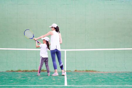 Mother and daughter practicing tennis Banque d'images - 132040762