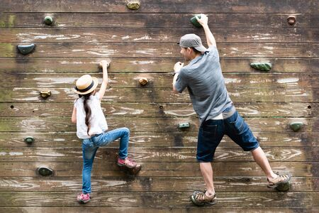 Father and daughter climbing the wall