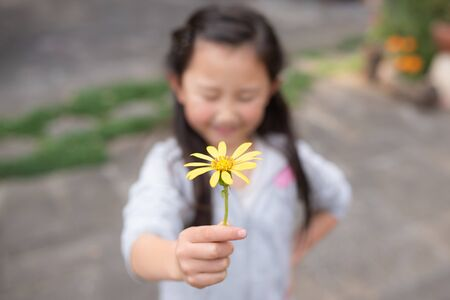 Girl holding out yellow flowers