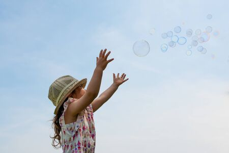 Toddler girl playing with soap bubbles Stock Photo
