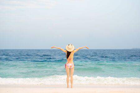 Japanese woman wearing bikini is relaxing on the beach