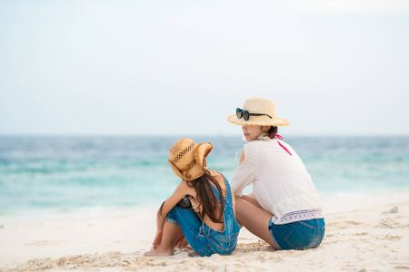 Mother and daughter sitting on sandy beach and speaking
